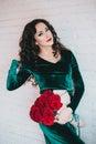 Härlig kvinna i en grön klänning och röda skor med röda rosor Royaltyfria Bilder