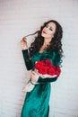 Härlig kvinna i en grön klänning och röda skor med röda rosor Arkivbild