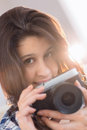 Hübscher brunette der ein foto mit retro kamera auf couch macht Lizenzfreie Stockbilder