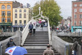 Ha penny bridge dublin ireland october pedestrian are crossing the liffey river through the when coming from temple bar Stock Images
