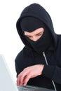 Hacker in balaclava typing on laptop Royalty Free Stock Photo