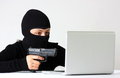Hacker female wit mask pointing a gun on a laptop isolated on a white background Royalty Free Stock Photos