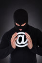 Hacker with an internet domain symbol dressed in black wearing a balaclava a white Stock Photos
