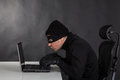 Hacker stealing data from a laptop on black background Stock Photography