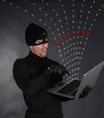 Hacker stealing data from a laptop on black background Royalty Free Stock Photo