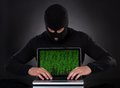 Hacker stealing data of a laptop computer in balaclava standing in the darkness furtively off or inserting spyware in an online Stock Photos