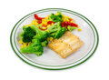 Haddock dinner with vegetables a small piece of broccoli red peppers and corn on a green striped plate Royalty Free Stock Image
