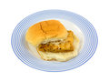 Haddock on white bun a portion of microwaved between a bread a blue striped plate Royalty Free Stock Photos