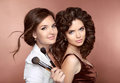 Hair beautiful two brunette smiling girls makeup artist with b brush hairstyle attractive young women posing at camera Stock Image