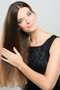 Hair care vertical portrait of a young woman taking of her long against a grey background Royalty Free Stock Photos
