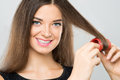 Hair curling close up portrait of a cheerful young woman her long over a grey background Royalty Free Stock Image