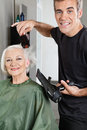Hair stylist blow drying senior woman s hair portrait of happy in salon Stock Photo