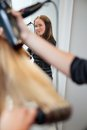 Hair stylist holding blow dryer mirror reflection of a beautiful professional Stock Images