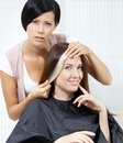 Hair stylist tries lock of dyed hair on the client blond sitting chair in hairdressing salon Royalty Free Stock Photo
