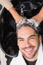 Hair stylist washing mans hair at the salon Stock Photography