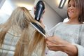 Hairdresser blow drying hair of female low angle view long blond with dryer and brush Stock Images