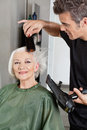 Hairdresser blow drying woman s hair male happy senior in beauty salon Royalty Free Stock Photo