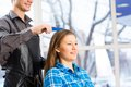 Hairdresser and client male puts woman s hair in a hairdressing salon Royalty Free Stock Images