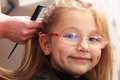 Hairdresser combing hair little girl child in hairdressing beauty salon Royalty Free Stock Photo