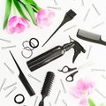 Hairdresser composition with spray, scissors, combs, barrette and tulips flowers on white background. Beauty concept. Flat lay, to Royalty Free Stock Photo