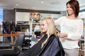 Hairdresser curling customer s hair stylist womans in beauty salon Royalty Free Stock Images