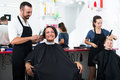 Hairdresser cutting hair of female client