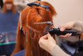 The hairdresser does hair extensions to a young, red-haired girl, in a beauty salon Royalty Free Stock Photo
