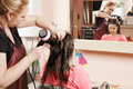 Hairdresser drying teenager girl s hairs against mirror Stock Photo