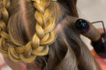 Hairdresser makes braids in beauty salon Royalty Free Stock Image