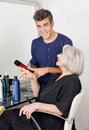 Hairdresser showing hair product to client portrait of male at salon Stock Photography