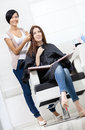 Hairdresser tries strand of dyed hair on the client beautician lock blond sitting chair in hairdress salon Royalty Free Stock Images