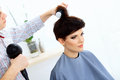 Hairdresser using dryer on woman wet hair brunette with short in salon Stock Photos