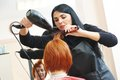 Hairdresser at work drying hair with blow dryer of women client beauty parlour after highlighting Royalty Free Stock Photo