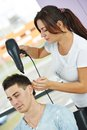 Hairdresser at work female drying hair with blow dryer of men client beauty parlour Royalty Free Stock Images