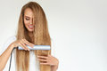 Hairdressing. Woman With Beautiful Long Hair Using Straightener Royalty Free Stock Photo
