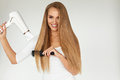 Hairdressing. Woman Drying Beautiful Healthy Long Straight Hair Royalty Free Stock Photo