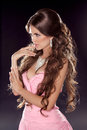 Hairstyle long wavy hair fashion photo of young woman sexy gi girl posing in pink dress isolated on dark background studio Stock Image