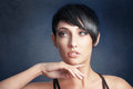 Hairstyle portrait of beautiful young woman with short black hair on dark blue background Royalty Free Stock Photography