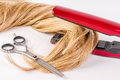 Hairstyling. Closeup blonde woman long haired making hairstyle iron. Damaged hair concept, scissors. Royalty Free Stock Photo