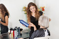 Hairstylist advising hair color to senior client female at beauty parlor Royalty Free Stock Photography