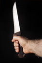 Hairy male hand holding a knife over a black background Royalty Free Stock Photo