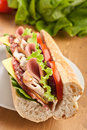 Half baguette meats sandwich of long tasty subway with lettuce tomatoes ham turkey breast salami and cheese isolated on white Royalty Free Stock Photo