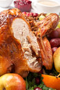 Half carved holiday roasted turkey close up with fruit and berries to serve Royalty Free Stock Photography