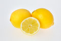 Half cut lemon fruit leaning against two whole oranges Stock Images