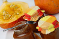 Half of cut pumpkin and three marmalade jars Royalty Free Stock Images