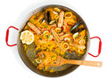 Half eaten paella top view of paellera of seafood and wooden skimmer on white background Royalty Free Stock Photography