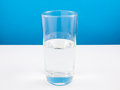 Half empty or half full glass of water on white table. (For positive thinking) Royalty Free Stock Photo