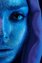 Half face of woman in blue and violet bodyart