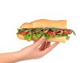 Half of french baguette sandwich in hand. Royalty Free Stock Photo
