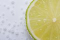 Half fresh lime in water with bubbles Royalty Free Stock Photo